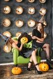 万圣夜服装的两名妇女在党坐在电灯泡背景的椅子 免版税库存图片