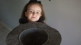 万圣夜服装的婴孩请求糖果 女孩在她的手,儿童笑上愉快地拿着一顶灰色呢帽 股票录像