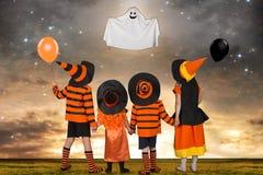 万圣夜服装的孩子看飞行鬼魂 图库摄影