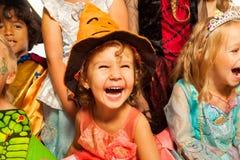 万圣夜服装的笑的女孩有朋友的 免版税库存图片