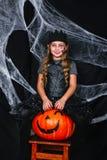 万圣夜服装的逗人喜爱的小女孩坐在背景的南瓜与蜘蛛网 免版税库存照片
