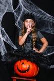 万圣夜服装的逗人喜爱的小女孩坐在背景的南瓜与蜘蛛网 免版税图库摄影
