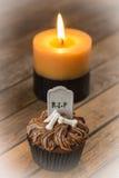 万圣夜杯形蛋糕和一个灼烧的蜡烛与渐晕作用 库存照片