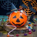 万圣夜杰克o溢出用糖果,在背景,正方形的鬼的万圣夜装饰的灯笼桶 免版税图库摄影