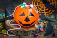 万圣夜杰克o溢出用糖果,在水平的背景的鬼的装饰的灯笼桶 库存照片