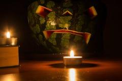 万圣夜标志、西瓜与被雕刻的红色微笑的面孔和灼烧的蜡烛在黑暗的背景 库存图片