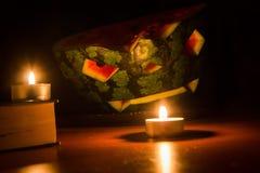 万圣夜标志、西瓜与被雕刻的红色微笑的面孔和灼烧的蜡烛在黑暗的背景 库存照片