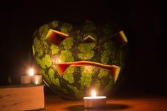 万圣夜标志、西瓜与被雕刻的红色微笑的面孔和灼烧的蜡烛在黑暗的背景 免版税库存图片