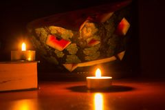 万圣夜标志,与被雕刻的红色微笑的面孔的西瓜 灼烧的蜡烛和书在木桌,黑暗的背景上 免版税库存照片