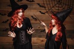 万圣夜概念-使用与不可思议的鞭子的一点红色头发巫婆魔术对她的有震惊表示的母亲 图库摄影