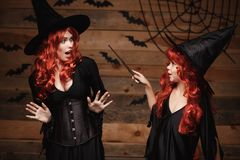 万圣夜概念-使用与不可思议的鞭子的一点红色头发巫婆魔术对她的有震惊表示的母亲 免版税图库摄影