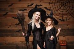 万圣夜概念-快乐的巫婆服装的庆祝万圣夜的母亲和她的女儿摆在用弯曲的南瓜在棒 图库摄影
