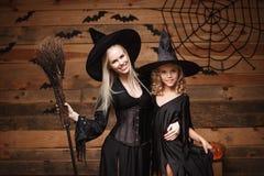 万圣夜概念-快乐的巫婆服装的庆祝万圣夜的母亲和她的女儿摆在用弯曲的南瓜在棒 免版税库存照片