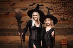 万圣夜概念-快乐的巫婆服装的庆祝万圣夜的母亲和她的女儿摆在用弯曲的南瓜在棒 免版税库存图片