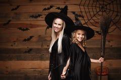 万圣夜概念-快乐的巫婆服装的庆祝万圣夜的母亲和她的女儿摆在用弯曲的南瓜在棒 库存照片
