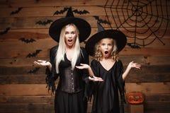 万圣夜概念-快乐的母亲和她的女儿冲击与某事的巫婆服装的 库存照片