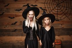 万圣夜概念-快乐的母亲和她的女儿冲击与某事的巫婆服装的 库存图片