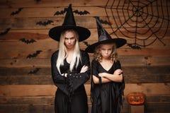万圣夜概念-快乐的母亲和她的女儿失望对某事的巫婆服装的 库存图片