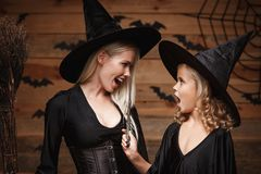 万圣夜概念-特写镜头美丽的白种人巫婆服装的庆祝万圣夜的母亲和她的女儿摆在与弯曲 库存照片