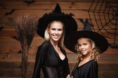 万圣夜概念-特写镜头美丽的白种人巫婆服装的庆祝万圣夜的母亲和她的女儿摆在与弯曲 图库摄影