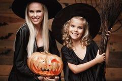 万圣夜概念-特写镜头美丽的白种人巫婆服装的庆祝万圣夜的母亲和她的女儿摆在与弯曲 免版税图库摄影