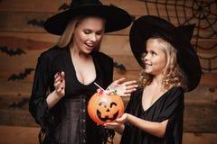 万圣夜概念-美丽的白种人巫婆服装的庆祝万圣夜与分享的母亲和她的女儿万圣夜能 库存图片