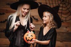 万圣夜概念-美丽的白种人巫婆服装的庆祝万圣夜与分享的母亲和她的女儿万圣夜能 库存照片