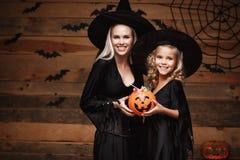 万圣夜概念-美丽的白种人巫婆服装的庆祝万圣夜与分享的母亲和她的女儿万圣夜能 免版税库存图片