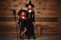 万圣夜概念-美丽的白种人有长的红色头发的在巫婆服装庆祝万圣夜摆在的母亲和她的女儿 图库摄影