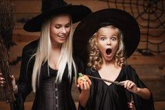 万圣夜概念-美丽的白种人母亲和她的女儿巫婆服装的喜欢使用魔术与不可思议的鞭子到万圣夜p 库存图片