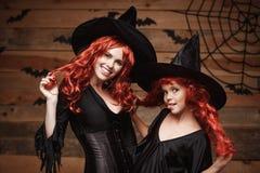 万圣夜概念-美丽的白种人母亲和她的女儿有长的红色头发的在巫婆服装庆祝 库存图片