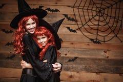 万圣夜概念-美丽的白种人母亲和她的女儿有长的红色头发的在巫婆服装愉快微笑和拥抱每ot 免版税库存图片