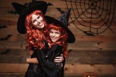 万圣夜概念-美丽的白种人母亲和她的女儿有长的红色头发的在巫婆服装愉快微笑和 免版税库存照片