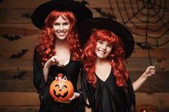 万圣夜概念-美丽的白种人母亲和她的女儿有长的红色头发的在巫婆服装用万圣夜糖果和魔术家 图库摄影