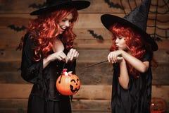 万圣夜概念-美丽的白种人母亲和她的女儿有长的红色头发的在巫婆服装用万圣夜糖果和魔术家 库存照片
