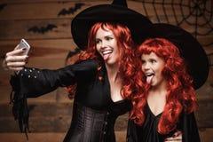 万圣夜概念-美丽的白种人母亲和她的女儿有长的红色头发的在采取一selfie与smartpho的巫婆服装 库存图片