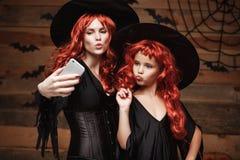 万圣夜概念-美丽的白种人母亲和她的女儿有长的红色头发的在采取一selfie与smartpho的巫婆服装 免版税库存照片