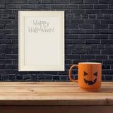 万圣夜模板的海报嘲笑 作为起重器o灯笼南瓜的咖啡杯在黑砖墙的木桌上 免版税库存照片