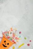 万圣夜橙色桶用糖果和枣 免版税库存照片
