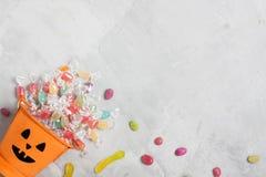 万圣夜橙色桶用糖果和枣 免版税库存图片