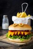 万圣夜汉堡妖怪用在木头的炸薯条 免版税库存图片