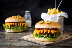 万圣夜汉堡妖怪用在木头的炸薯条 免版税库存照片