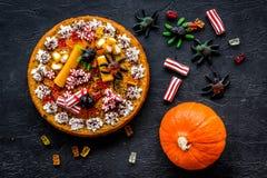 万圣夜甜点 南瓜饼和胶粘的图在黑背景顶视图 库存照片