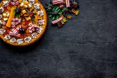 万圣夜甜点 南瓜饼和胶粘的图在黑背景顶视图copyspace 库存图片