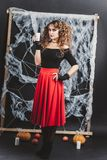 万圣夜站立在女衬衫和红色裙子的黑墙壁前面的巫婆女孩 举蜡烛手中 图库摄影