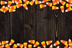 万圣夜糖味玉米在黑暗的木头的双边界 免版税库存照片