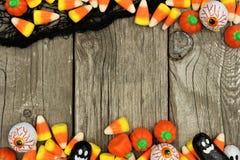 万圣夜糖果和黑布料加倍边界反对土气木头 免版税图库摄影