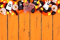 万圣夜糖果在老橙色木头的上面边界 免版税库存图片
