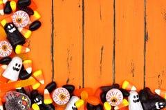 万圣夜糖果在老橙色木头的角落边界 图库摄影