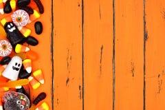 万圣夜糖果在老橙色木头的边边界 图库摄影